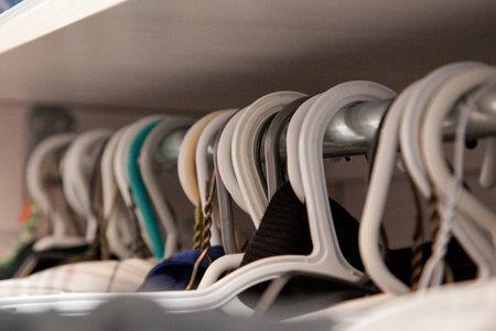 Plastic white hangers in a row in the closet Stock Photo - 113086349