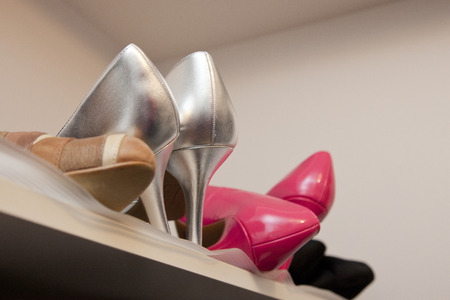 Collection of heels and shoes on top shelf of closet Stock Photo - 113086352