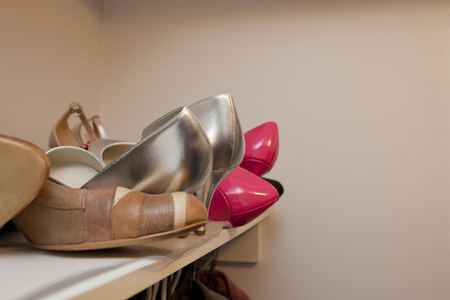 Silver, pink and brown shoes on the top sheld of a closet Stock Photo - 113086354