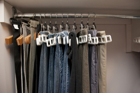 Pairs of jeans and pants hang on hangers in a row in the closet, well organized Stock Photo - 113086357