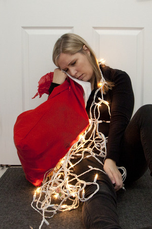 A woman has fallen asleep next to a bundle of christmas lights and a red santa sack