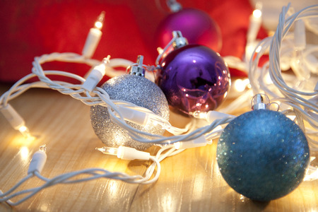Blue, silver and purple christmas ornaments entangled in white lights