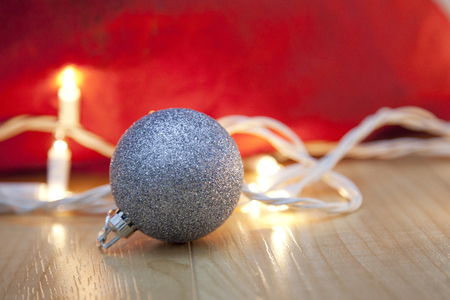 Red bag with white twinkling christmas lights and a silver ornament Stock Photo - 113086388