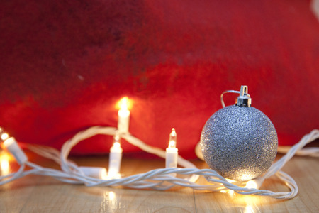 Festive holiday scene with copy space, showing white twinkly lights and sparkly silver ball Stock Photo - 113086389