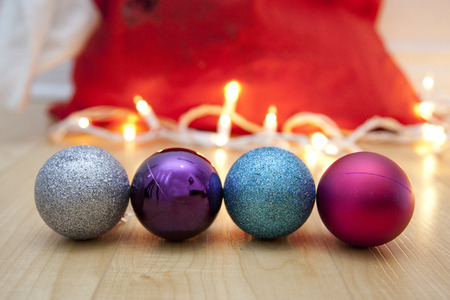 Four holiday ornaments on the floor with white lights and a red bag Stock Photo - 113086390