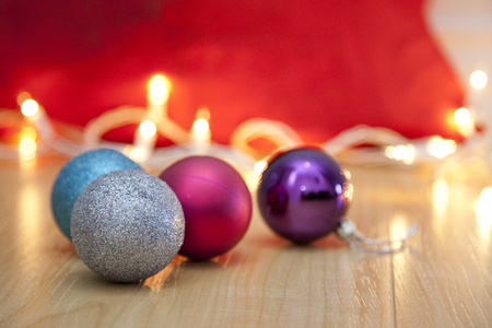 Colored christmas ornaments with white twinkling lights beside a red bag Stock Photo - 113086393