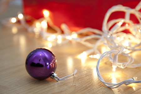 Purple round glass christmas ball on the floor with white holiday lights Stock Photo - 113086397