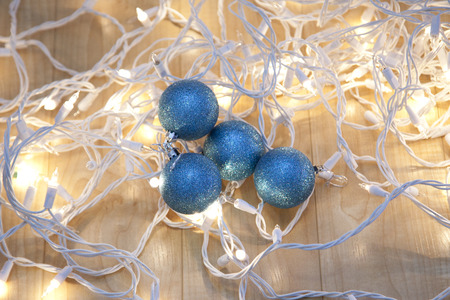 White holiday lights tangled up with four sparkly blue christmas balls Stock Photo - 113086405