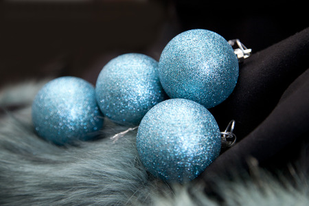 Sparkly blue holiday ornaments on black and green furry background Stock Photo