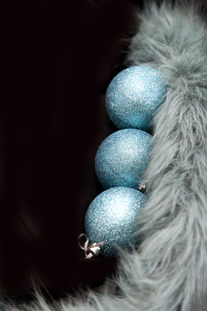 Three blue holiday ornaments in a vertical row on black copy space Stock Photo - 113086416