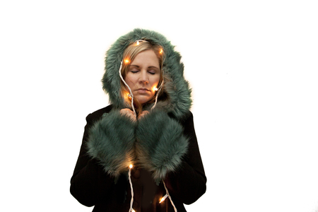 Model in beautiful coat with fancy trim has holiday lights wrapped around and eyes closed, dreaming