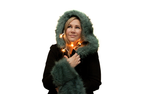 Model in festive green furry coat and holiday lights looking up happily thinking of the holidays Stock Photo - 113086417