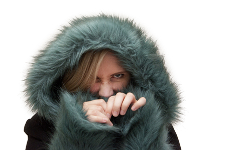 Beautiful blond woman in studio has a green fur hood pulled up and is hiding and making angry face