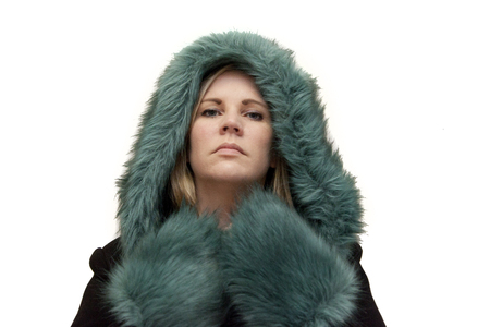 Blonde model in a beautiful green and black fur coat with serious face is ready for winter Stock Photo - 113086422