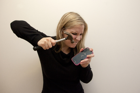 An angry woman takes a hammer and smashes her cell phone Stock Photo - 113086427