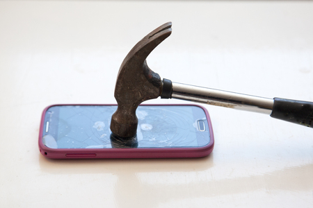 Taking a hammer and smashing a cell phone