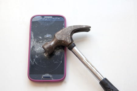 Hammer has been taken to a cell phone and cracked it Stock Photo - 113086431