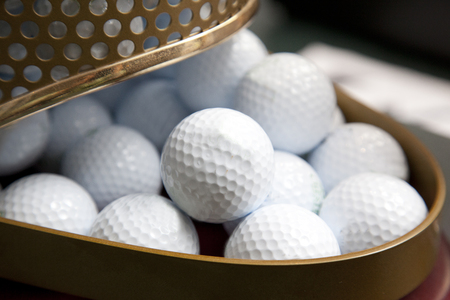 A container of white golf balls at a pro shop ready for sale or to be owned Zdjęcie Seryjne