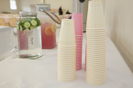 pink and white plastic cups ready to be filled from a container of cucumber water