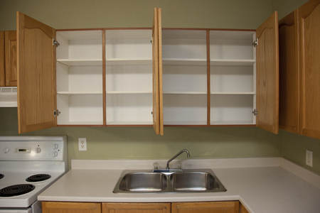 Kitchen counter beside a kitchen sink with two empty cabinets above in a home or apartment 写真素材