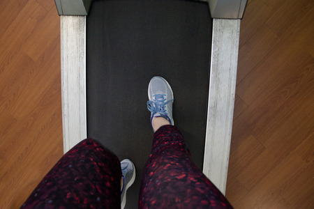 Looking down at a pair of legs and sneakers ready to run on a treadmill Stock Photo