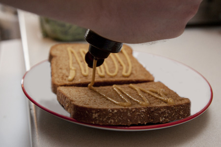 A person is pouring mustard onto their bread to make a sandwich