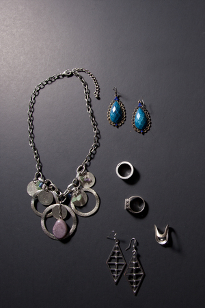 Various rings, earrings and a necklace against a black background 写真素材