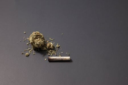 a small amount of pot on a black background and a joint thats already been partly finished