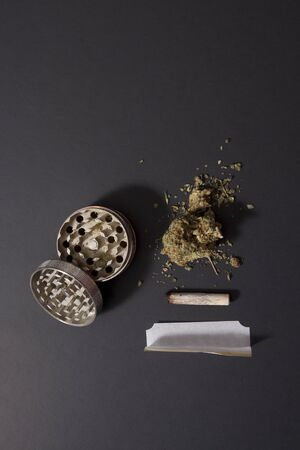 view with copy space of a partially smoked joint, with rolling papers and pot and a grinder Фото со стока