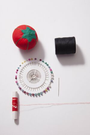 White copy space with red thread and push pins and cushion, sewing supplies