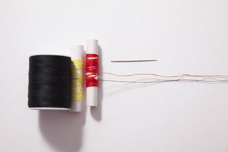 Various sizes and colours of thread and a needle spread long against a white backdrop Фото со стока