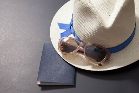 Passport, hat and sunglasses on a black background