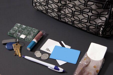 lipstick, tissue, a purse, gum, coins, pen, and keys Фото со стока