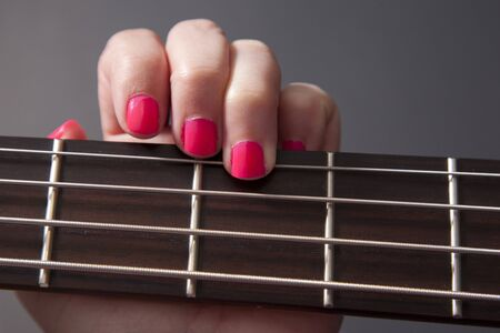 Hand with pink nail polish playing the fret on a bass guitar Фото со стока