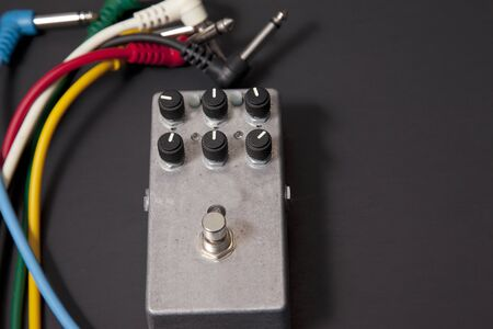 A metal distortion pedal with pots and several colorful cables on black background Фото со стока