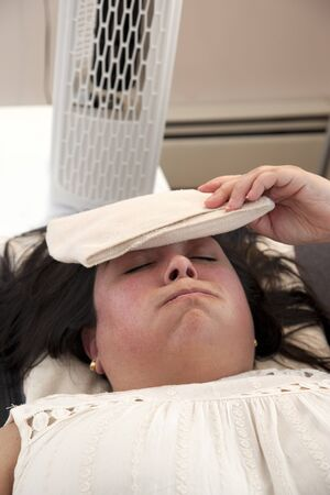 Woman lays in front of the fan with an ice pack on her forehead on a swealtering day