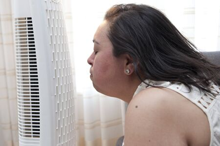 Woman enjoys the cool breeze of a fan at home in the heat