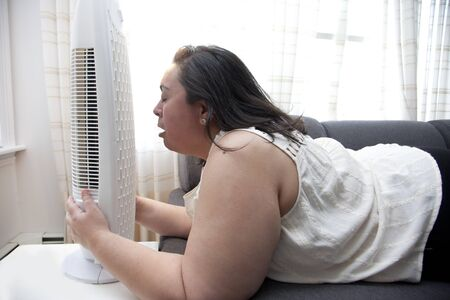 Person with heat exhaustion clings to their fan inside at home 写真素材