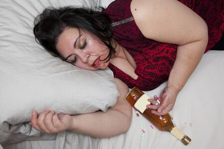 Woman is sloppy passed out or overdosed in bed with a bottle of booze and pills in her hand