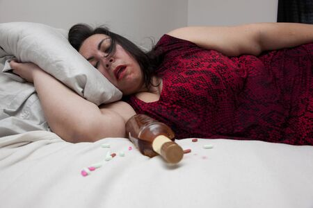 Person passed out from too much alcohol at home on their bed Фото со стока - 129928552