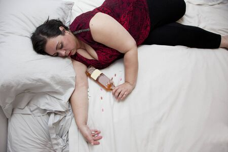 A hot mess of a woman has overdosed or passed out with her liquor Фото со стока - 129928554