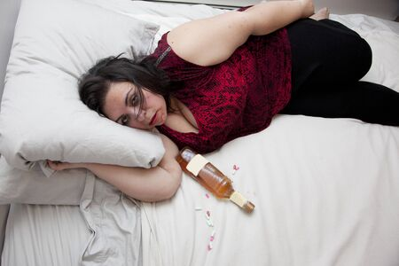 Woman sloppy or drunk in bed with a bottle and pills with copy space on bed
