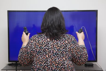 addicted to video games, a woman holds two controllers in her hands at home