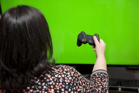 against a green screen, a woman holds a video game controller with one hand