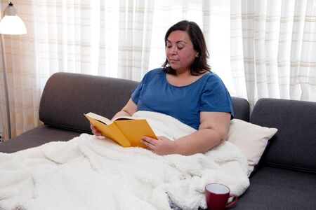 Real woman relaxing on her couch with a book and mug