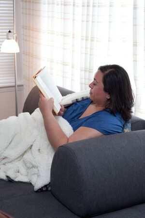 Woman comfortable and happy at home with a soft blanket and a good book