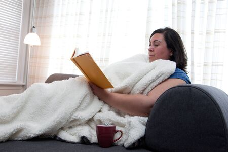 A single woman reads a book, happy to be at home alone with a blanket and warm drink Stok Fotoğraf