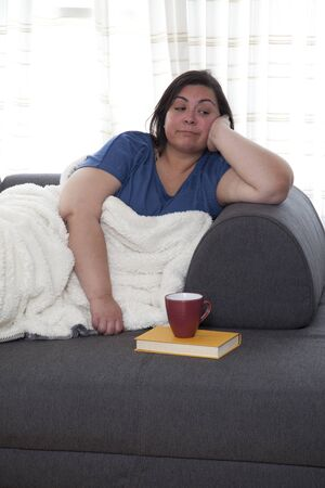 Woman sitting on her couch having finished her book and drink and is now bored and alone Фото со стока