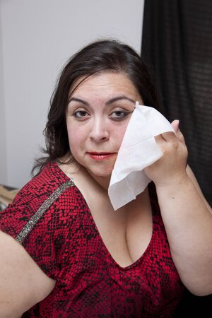 Latina woman takes off her dark smeared eye makeup with a wipe