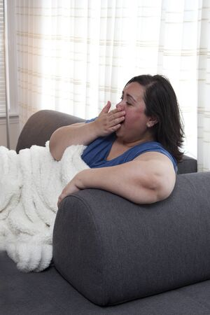 Woman is sleepy or bored, yawning on the sofa at home